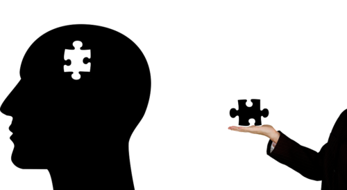 A woman holding a puzzle piece and a silhouette of a man's head that can symbolize addressing of teen mental health